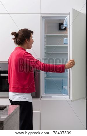 Terrified Woman Against The Empty Fridge