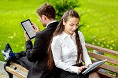 pic of work bench  - Young Business couple sitting on the bench and reading or working with tablets outdoors - JPG