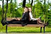 image of work bench  - Young Business couple sitting on the bench and reading or working with tablets outdoors - JPG