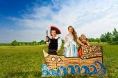 picture of pirate sword  - Kids play pirate with sword and two princesses stand together on the carton ship and smile - JPG