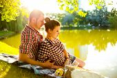 foto of love bite  - happy young couple bite grapes and enjoying picnic