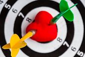 foto of bullseye  - Closeup of black and white target with two darts in red valentine heart love symbol as bullseye.  ** Note: Shallow depth of field - JPG