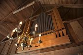 image of pipe organ  - Pipe organ in an old wooden chapel with a pendant light - JPG