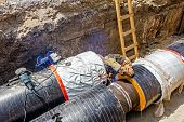 pic of pipe-welding  - Metal worker welds two big metal pipes on a construction site - JPG