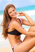 stock photo of one piece swimsuit  - An attractive young woman wearing a bikini is sitting on the beach with the surf in the background and smiling at the camera. Vertical shot.