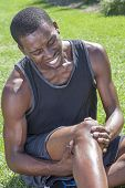 stock photo of knee-cap  - Young lean African American athlete in shorts and tank top sits on grass clutching injured knee and showing painful facial expression - JPG