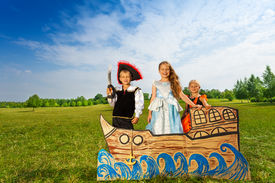 foto of pirate sword  - Kids play pirate with sword and two princesses stand together on the carton ship and smile - JPG