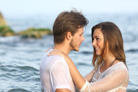 stock photo of bathing  - Profile of a young couple in love bathing in the sea in the beach - JPG