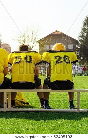 College Football Team Sitting On The Bench