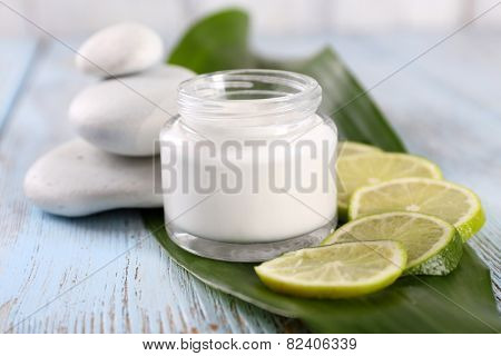 Cosmetic cream with slices of lime and spa stones on wooden background