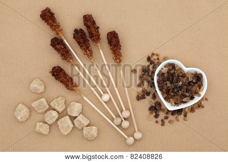 Brown sugar cubes, lollipops and crystal chunks over brown paper background.