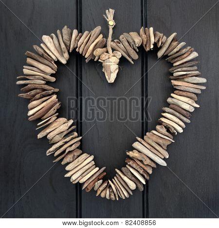 Driftwood heart hanging on a dark oak wood background.