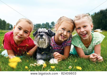 Group Of Happy Children Playing On Green Grass In Spring Park
