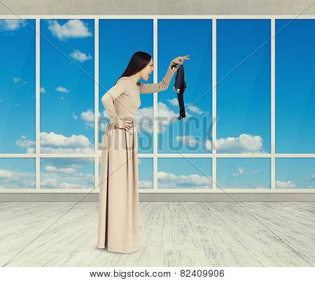 aggressive woman holding small man and yelling. photo in room with big windows