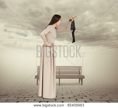 angry young woman holding small man and screaming at him. photo at outdoor