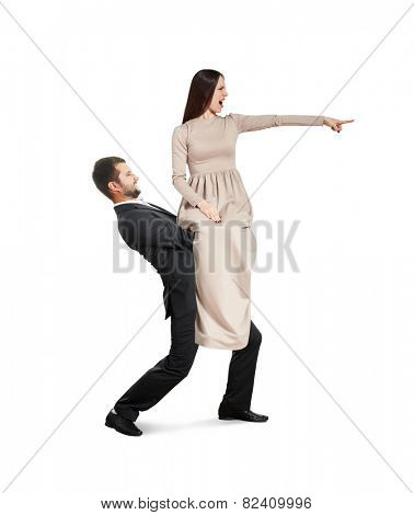 tired young man holding beautiful yelling woman and going forward. isolated on white background