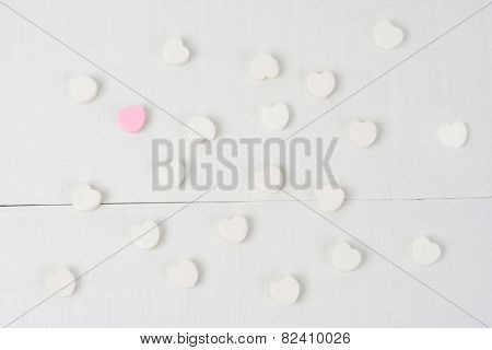 Overhead shot of a group of white Valentine's Day candy hearts on a white wood table with one lone pink heart. Horizontal format.