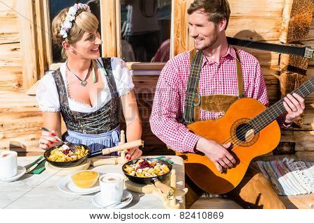 Couple on mountain hut eating Kaiserschmarrn, a traditional Austrian pancake