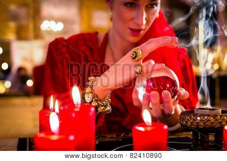 Fortuneteller or esoteric Oracle, sees in the future by looking into their crystal ball, incense burning and candles giving light
