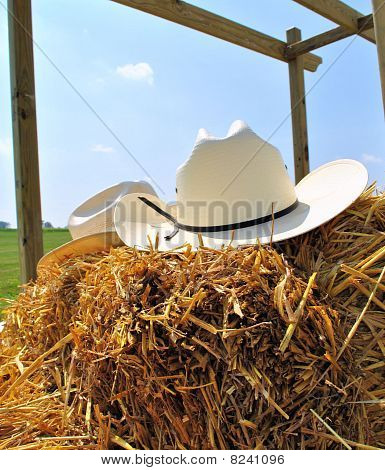Cowboy hats on a hay bail