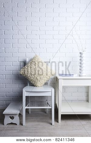 Modern interior with chair and pillow on white brick wall background