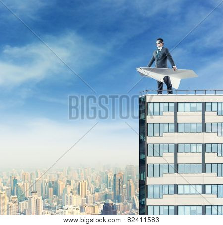 Man with paper plane on the roof
