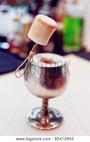 Cocktail with marshmallow in old metal goblet, toned image, selective focus