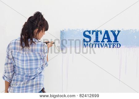 Woman painting wall blue against stay motivated