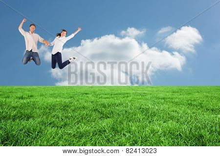 Couple jumping and holding hands against cloudy sky