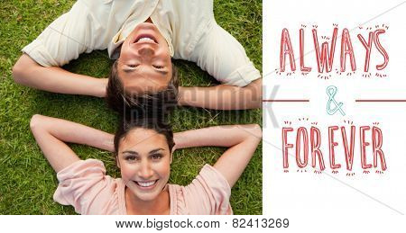 Two friends smiling while lying head to head with both hands behind their neck against always and forever