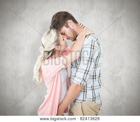 Attractive young couple about to kiss against white background