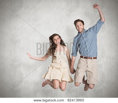 Cheerful young couple jumping against weathered surface