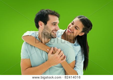 Cute couple smiling at each other against green vignette
