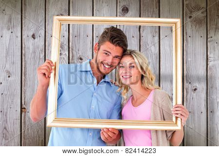 Attractive young couple holding picture frame against wooden planks