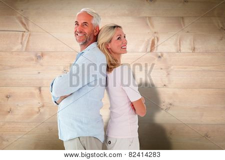 Smiling couple standing leaning backs together against bleached wooden planks background