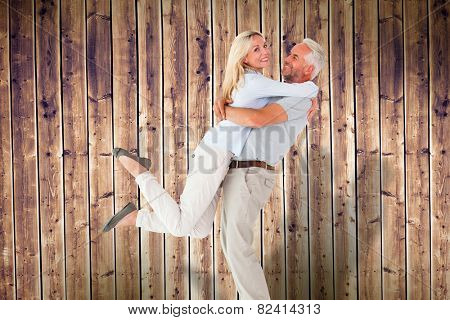 Man picking up his partner while hugging here against wooden planks background