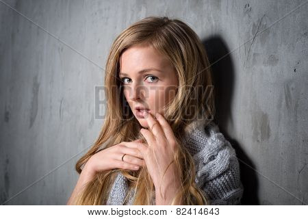 Sexy young longhair blonde woman in knitted sweater posing against grungy gray wall. Scared or resen