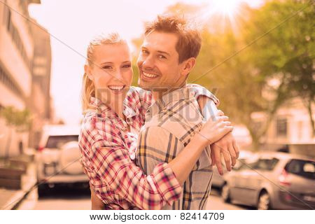 Couple in check shirts and denim hugging each other on a sunny day in the city