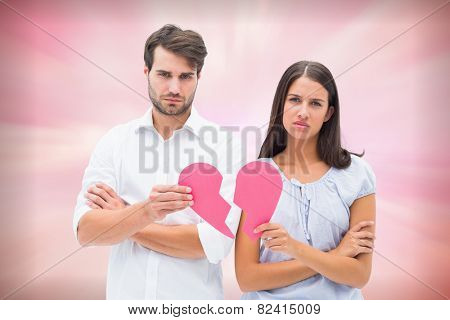 Upset couple holding two halves of broken heart against digitally generated pink girly design
