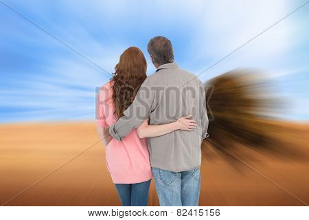 Casual couple standing arms around against sunny brown landscape