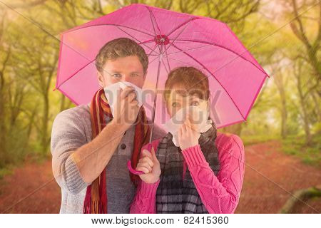 Couple standing underneath an umbrella against peaceful autumn scene in forest