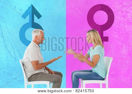 Unhappy couple sitting on chairs having an argument against pink and blue