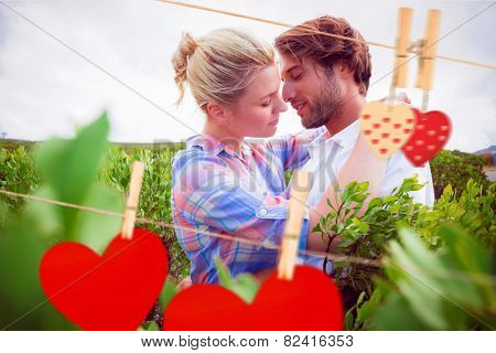 Smiling couple embracing outside among the bushes against hearts hanging on the line