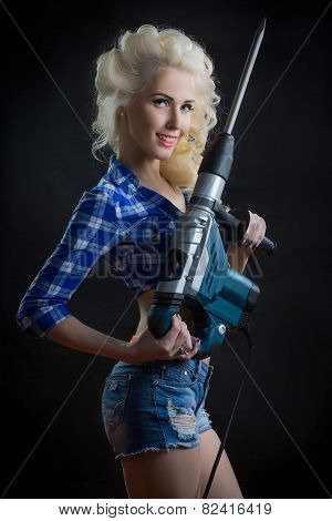 blonde with industrial hammer. dark background.