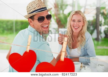 Hip young couple having coffee together against hearts hanging on a line