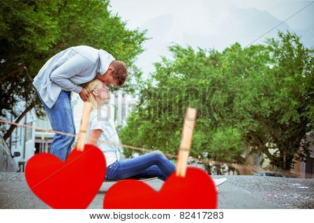 Hip young blonde sitting on skateboard with boyfriend kissing forehead against hearts hanging on a line