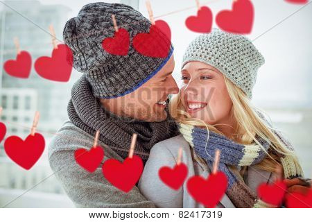 Cute couple in warm clothing smiling at each other against hearts hanging on a line