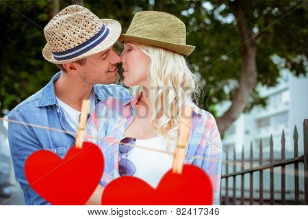 Hip young couple kissing by railings against hearts hanging on a line