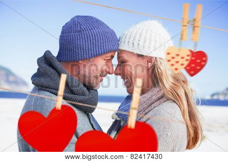 Attractive couple smiling at each other on the beach in warm clothing against hearts hanging on the line
