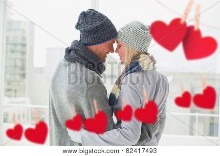 Cute couple in warm clothing hugging against hearts hanging on a line
